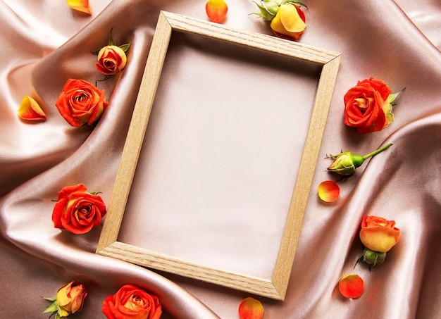 Flowers composition and red roses on beige silk background