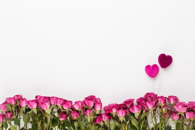Композиция цветов. красные розы на белом фоне деревянных. плоская планировка, вид сверху.