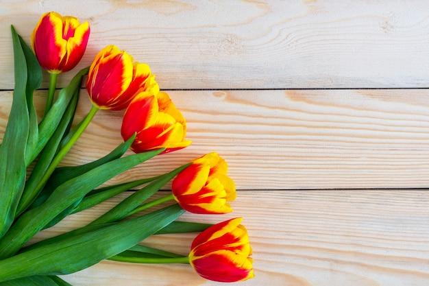 花の構成。コピースペースと木製の背景に赤いチューリップの花。