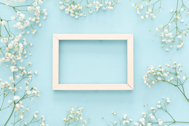 Flowers composition romantic. white gypsophila flowers, photo frame on pastel blue background
