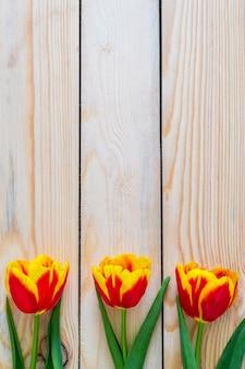 花の構成。木製の背景に春の赤いチューリップの花