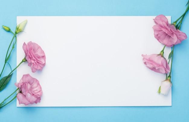 Композиция цветов. венок из розовых цветов с белой бумажной картой на синем фоне. плоская планировка, вид сверху, копия пространства.