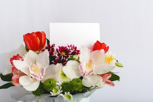 花おめでとう。白い背景の上の花束の花でお祝いカード。テキスト、フレームのスペースを持つ空白のカード。蘭、チューリップ、ギフトカードと春のお祝い花のコンセプト