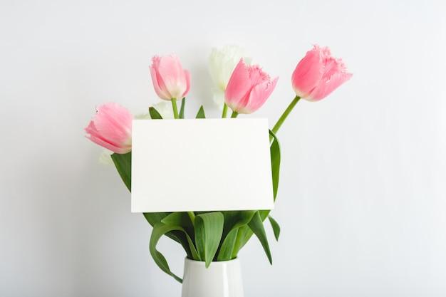 花おめでとう。白地にピンクのチューリップの花束でお祝いカード。テキスト、フレームのためのスペースを持つ白い空白のカード。春のお祝い花のコンセプト、ギフトカード。