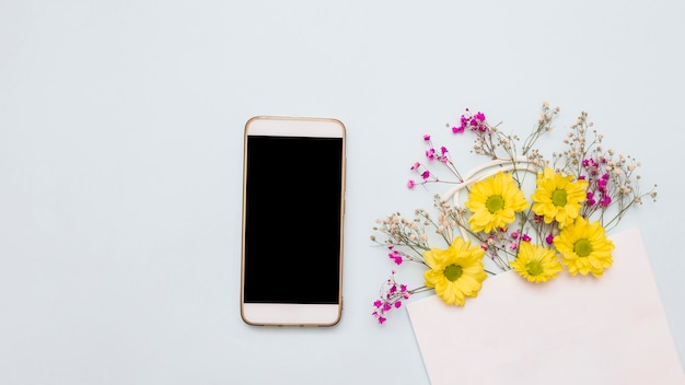 Flowers decorated paper bag and smartphone on white backdrop