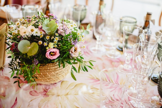 Flowers decorating the centerpieces with luxury cutlery on the tables of a wedding hall.
