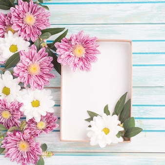 Flowers decoration with an empty box on wooden backdrop