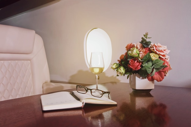 Цветы, дневник, бокал вина на рабочем столе роскошного интерьера в частном самолете. современный и удобный бизнес-самолет с декором. концепция качества обслуживания пассажиров в авиационной отрасли на высшем уровне