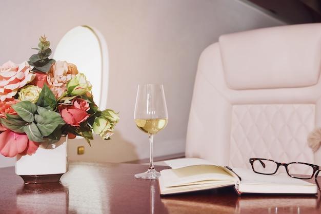 Цветы, дневник, бокал вина на рабочем столе роскошного интерьера в частном самолете