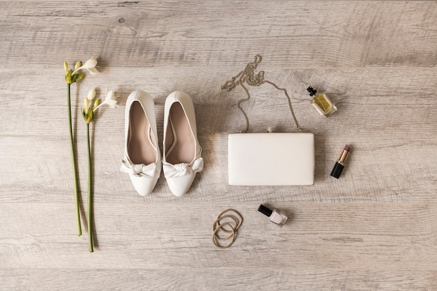 Flowers; dress shoes; clutch; perfume; lipstick; nail varnish and hairbands on wooden backdrop