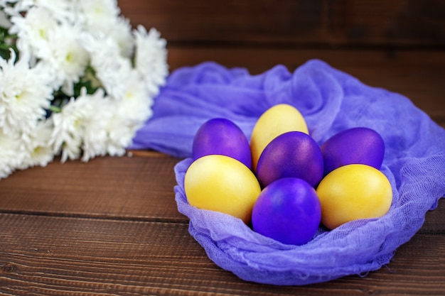 Flowers and eggs on a wooden background. concept happy easter.