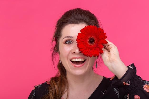 꽃, 감정과 사람들 개념-여자는 분홍색 벽에 거베라와 그녀의 눈을 감았