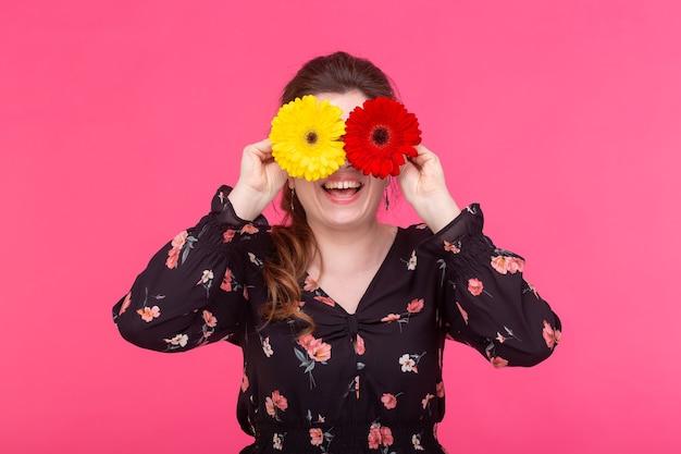 꽃, 감정과 사람들 개념-여자는 분홍색 표면에 gerberas와 함께 그녀의 눈을 감았