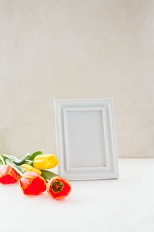 Flowers and empty photo frame placed near wall