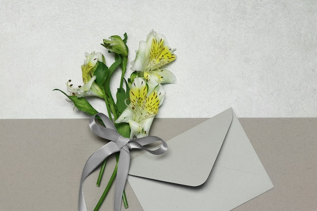 Flowers and envelope on grey beige background