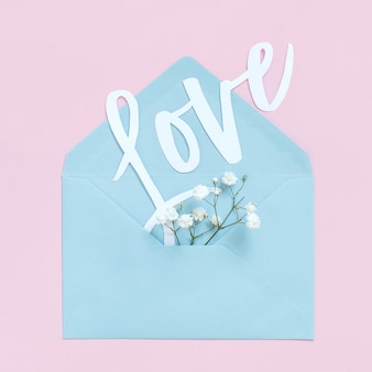 Flowers, envelope and word love on a light pink background top view