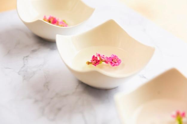 Цветы, плавающие в чашах воды в спа-салоне