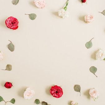 Flowers frame made of beige and red roses, eucalyptus leaf on pale pastel beige. flat lay, top view. floral wreath frame.