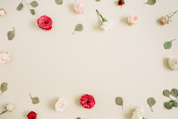 ベージュと赤いバラで作られた花のフレーム、淡いパステルベージュにユーカリの葉。フラットレイ、上面図。花の花輪フレーム。