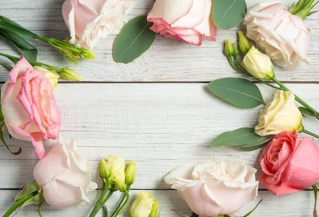 흰색 나무 누추한 배경에 꽃 프레임입니다. 크림 같은 eustoma, 유칼립투스 및 분홍색 장미.