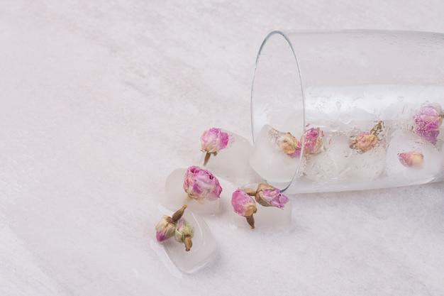 Fiori congelati in cubetti di ghiaccio sulla superficie bianca.