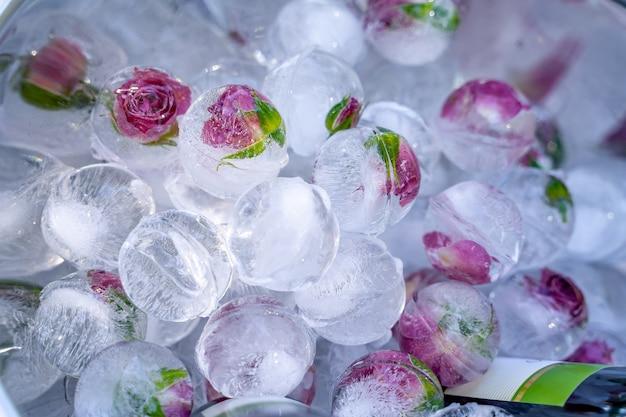 Цветы, замороженные в шариках изо льда на празднике. модное украшение стола. нежные сиреневые цветы во льду. крупный план.