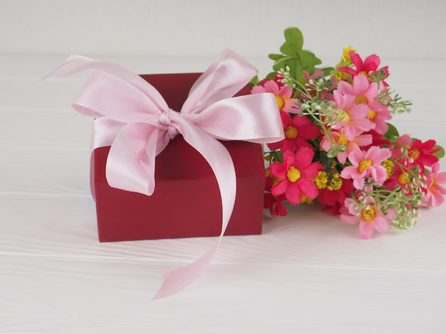Flowers and gift box on wooden rustic table. mother or valentines day greeting card. copy space for text.