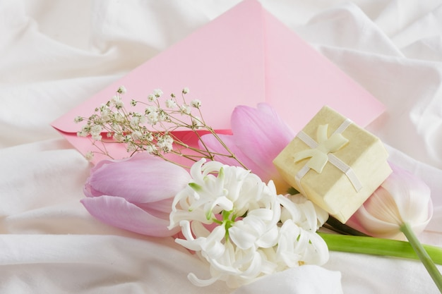 Flowers gift boxes pink envelope on the bed gift to woman concept