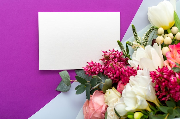 Flowers gift card. congratulations card in bouquet of roses, tulips, eucalyptus on purple background.