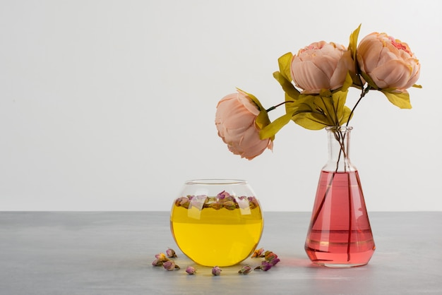 Flowers in glass vase and cup of green tea on grey table.