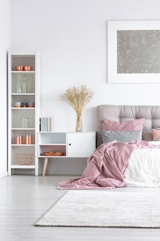 Flowers in glass vase on white cupboard between high shelf with copper accessories and king-size bed with pastel pink quilt