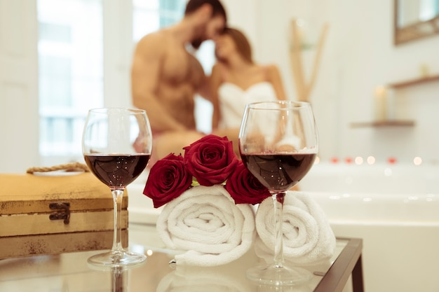 Flowers and glasses of drink near couple kissing in spa tub