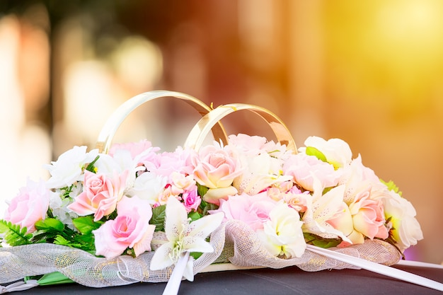 Flowers and golden rings wedding ornament decoration on a car limousine.