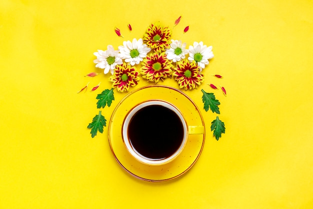Flowers, green leaves and cup of hot coffee