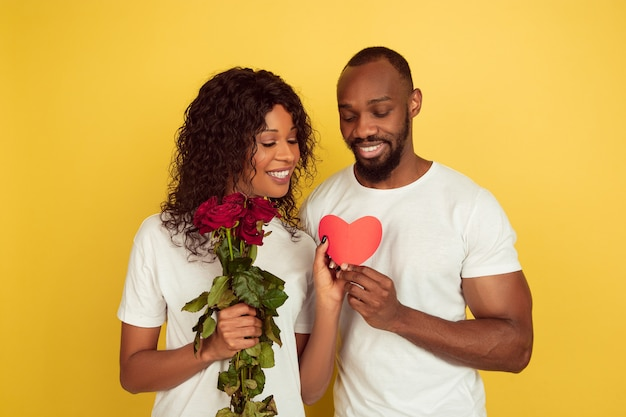 Flowers and heart. valentine's day celebration, happy african-american couple isolated on yellow studio background. concept of human emotions, facial expression, love, relations, romantic holidays.
