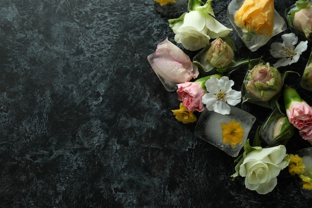 Flowers and ice cubes on black smokey background
