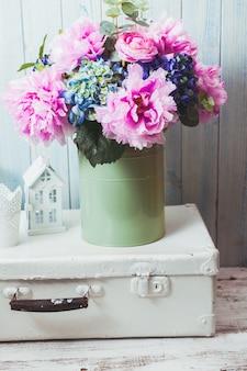 Цветы в синей винтажной банке на белой ретро-сумке и кухонной посуде
