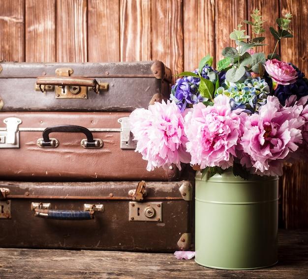 Цветы в зеленой винтажной банке и ретро чемоданы
