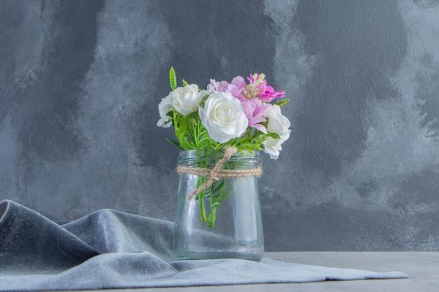 Цветы в банке на куске ткани, на белом столе.