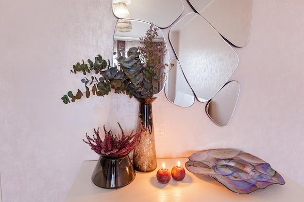 꽃병에 있는 꽃은 거울 배경에 있는 침대 옆 탁자에 있는 두 개의 촛불 근처에 서 있습니다. 벽 근처 장식.