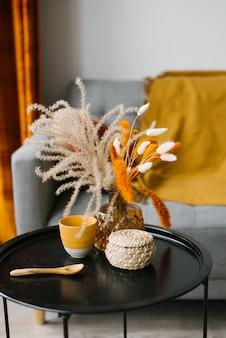 花瓶の花はブラックコーヒーテーブルの上に立っています。シンプルなスカンジナビアスタイルのリビングルームのインテリアの詳細