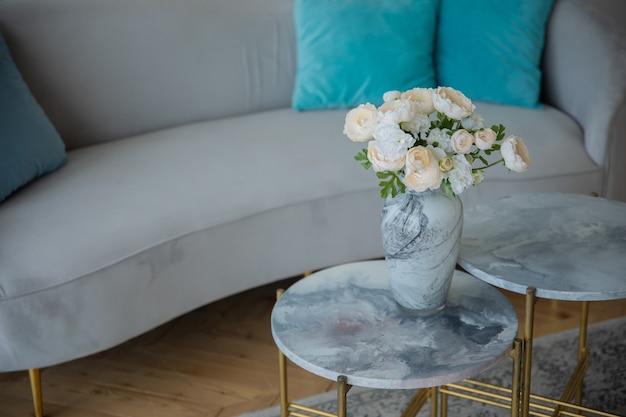装飾的なテーブルと灰色のソファの上の白い花瓶の花