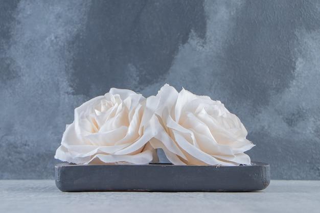 흰색 바탕에 나무 접시에 꽃. 고품질 사진