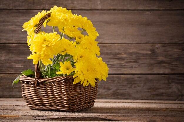 Цветы в корзине на деревянном фоне