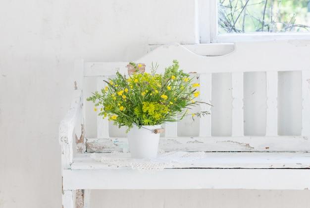 屋内の古い白い木製のベンチにバケツの花