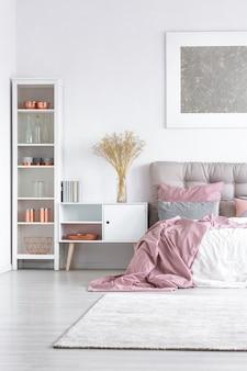 Цветы в стеклянной вазе на белом шкафу между высокой полкой с медными аксессуарами и большой кроватью с пастельно-розовым одеялом