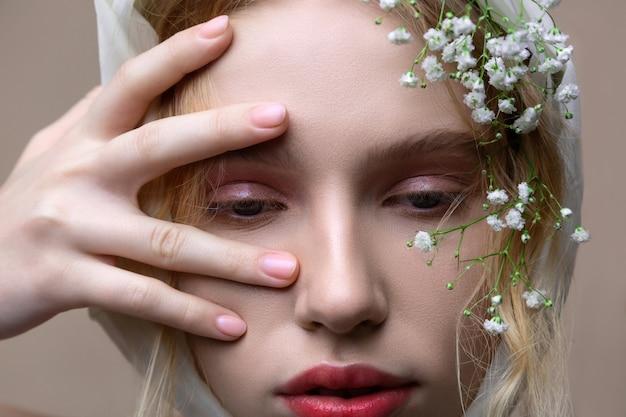 髪の花。彼女の髪に小さな白い花が壁の近くでプロのポーズをとっている魅力的なモデル