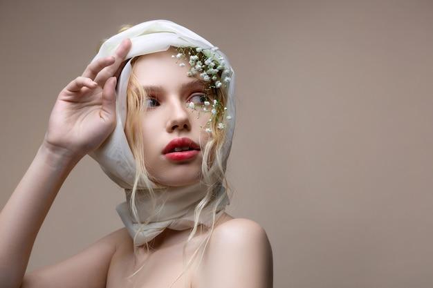 髪の花。淡いピンクの唇と髪の花でポーズをとるナチュラルメイクの青い目のモデル