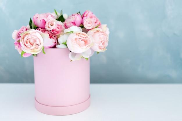丸い豪華プレゼントボックスの花。紙箱にピンクと白の牡丹の花束。テキストの無料copyspaceと花の帽子ボックスのモックアップ。パステルカラーのインテリア。