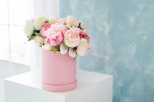 丸い豪華プレゼントボックスの花。窓の近くの紙箱にピンクと白の牡丹の花束。テキストの無料copyspaceと花の帽子ボックスのモックアップ。パステルカラーのインテリア。